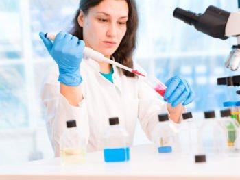 photo of woman working in lab performing tests for the genetics of cancer