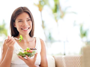 photo of woman eating a salad, good nutrition for gene expression