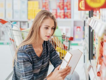 Young woman doing grocery shopping at the supermarket and reading a food label with ingredients on a box, using Nutrigenomics to inform health choices