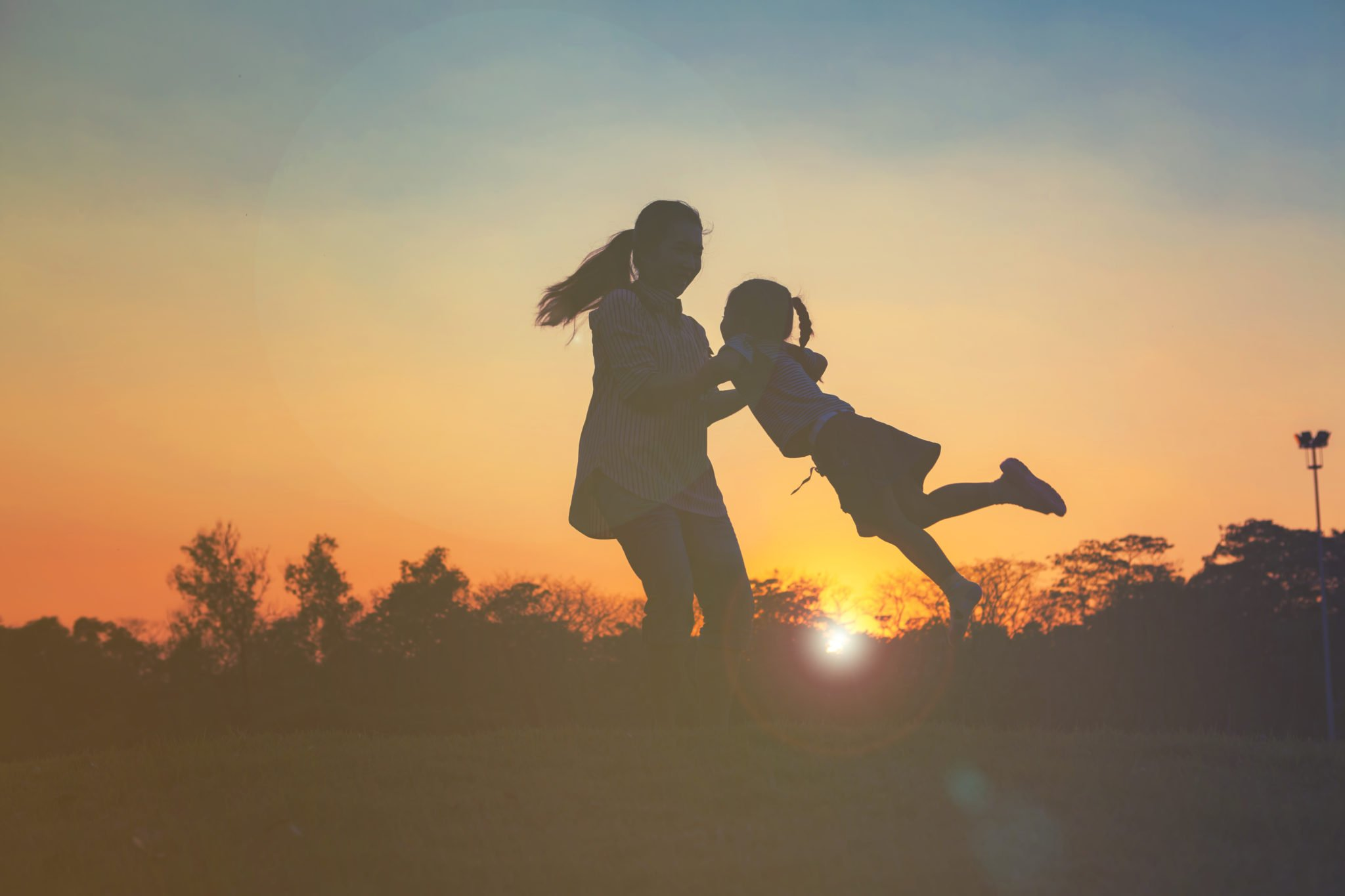 Silhouette of happy little girl child running into arms of his loving mother for hug with sun flare