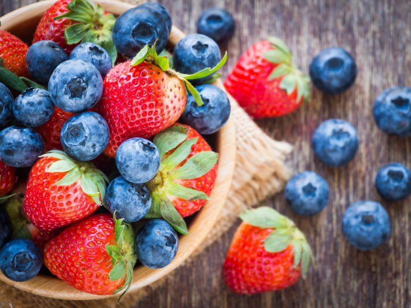 photo of Blueberries and strawberry in wooden bowl on wooden table background