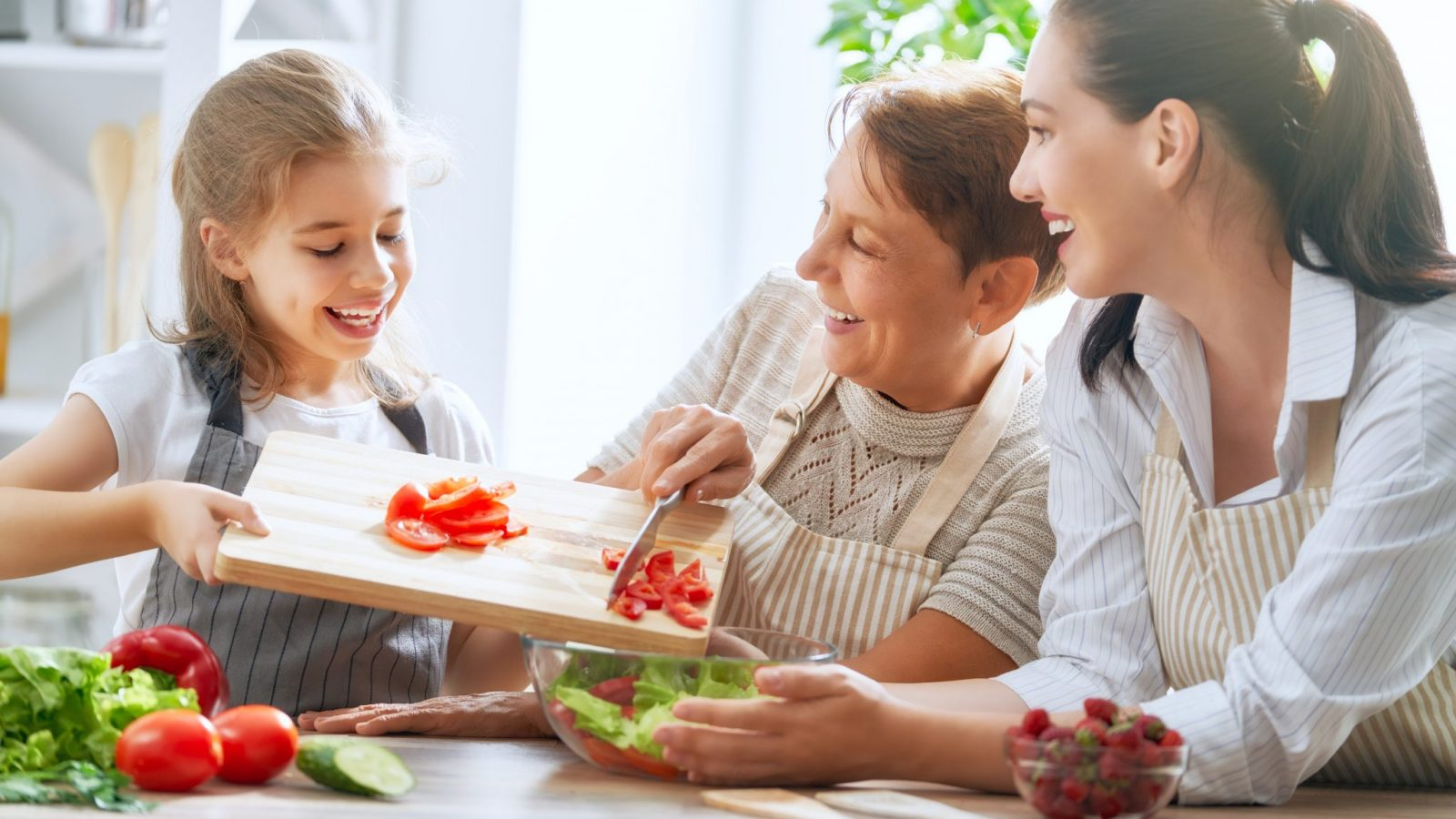 photo of grandmother, mother, and daughter preparing healthy foods together
