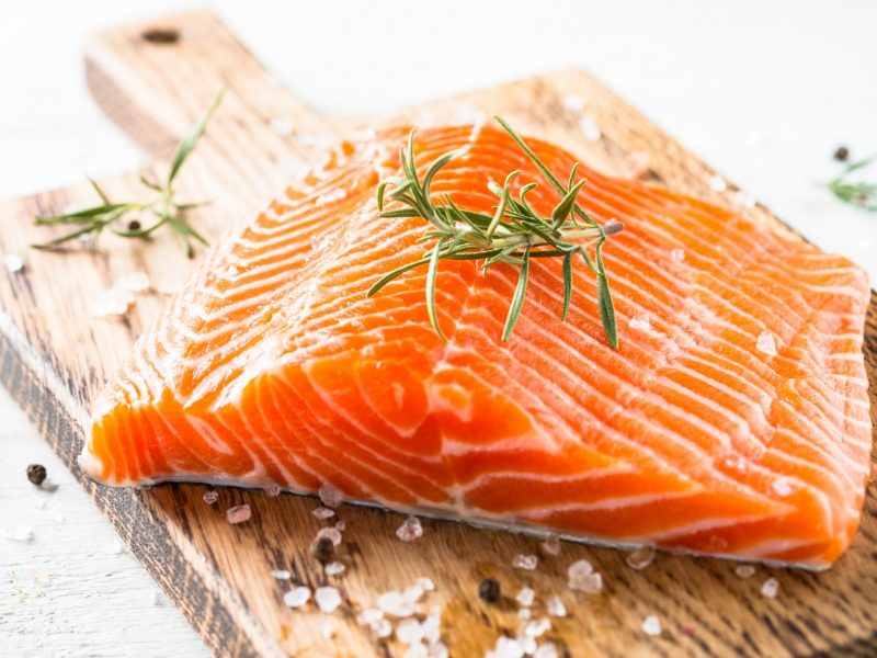 photo of Salmon fish. Uncooked salmon fillet with lemon sea salt and rosemary on white