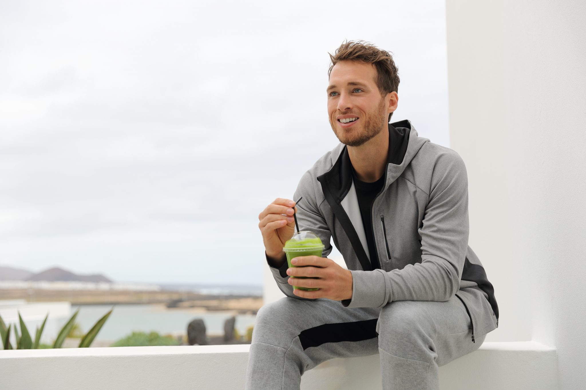 Photo of man sitting outside drinking green juice for a cleanse diet
